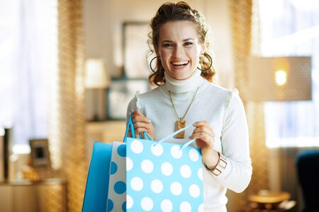 Portrait of smiling trendy 40 years old woman in white sweater and skirt with blue shopping bags in the modern living room in sunny winter day.