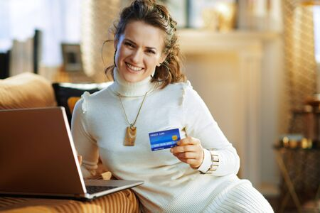 happy middle age housewife in white sweater and skirt with credit card making online purchases on e-commerce website at modern home in sunny winter day.