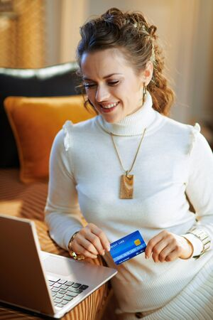 smiling elegant woman in white sweater and skirt with credit card buying on internet in the modern living room in sunny winter day.