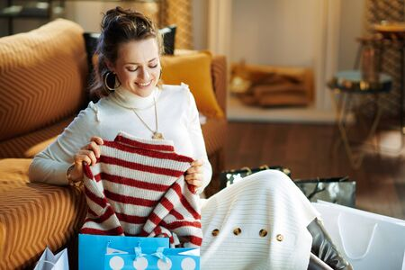 smiling trendy woman in white sweater and skirt sitting near sofa with shopping bags checking bought sweater at modern home in sunny winter day. Banque d'images
