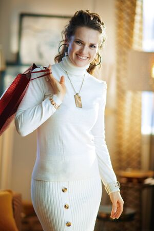 Portrait of happy trendy 40 years old housewife in white sweater and skirt with red shopping bag in the modern house in sunny winter day.