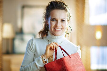 Portrait of happy middle age housewife in white sweater and skirt with red shopping bag at modern home in sunny winter day. Stockfoto