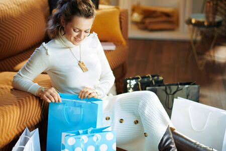 happy modern 40 years old woman in white sweater and skirt in the modern living room in sunny winter day sitting near couch looking inside shopping bag.