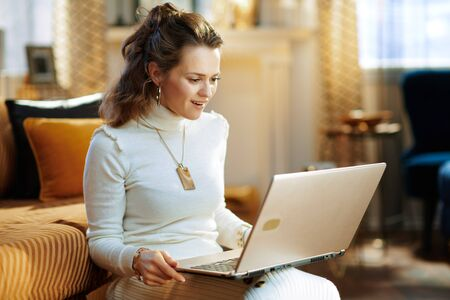 surprised elegant 40 years old housewife in white sweater and skirt in the modern living room in sunny winter day using website on a laptop.