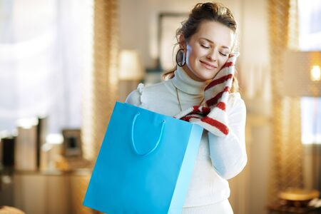 smiling trendy woman in white sweater and skirt with blue shopping bag enjoying purchased sweater at modern home in sunny winter day. Stockfoto