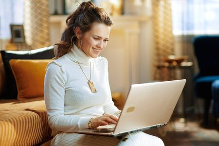 happy stylish 40 years old woman in white sweater and skirt with laptop at modern home in sunny winter day.