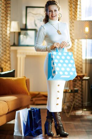 Full length portrait of happy stylish woman in white sweater and skirt with bags returned after shopping standing at modern home in sunny winter day.
