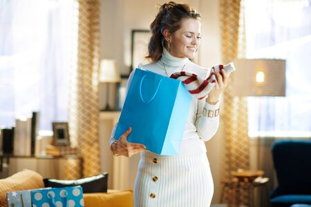 smiling stylish middle age woman in white sweater and skirt with blue shopping bag checking purchased sweater at modern home in sunny winter day. Stockfoto