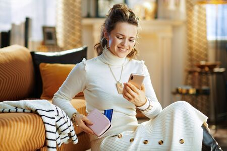Smiling elegant woman in white sweater and skirt with credit card sitting near couch looking for new sweater at fashion online shop on a smartphone in the modern living room in sunny winter day. Stockfoto
