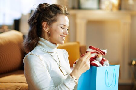 happy stylish female in white sweater and skirt sitting near couch with shopping bags checking purchased sweater in the modern house in sunny winter day.