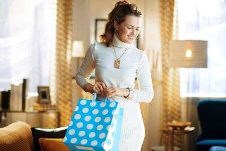 happy elegant middle age housewife in white sweater and skirt with blue shopping bags in the modern house in sunny winter day.