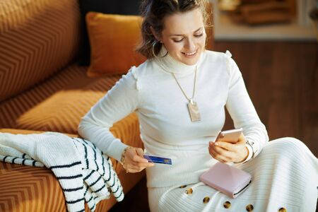 Smiling trendy housewife in white sweater and skirt with credit card sitting near couch looking for new sweater at fashion online shop on a smartphone in the modern living room in sunny winter day.