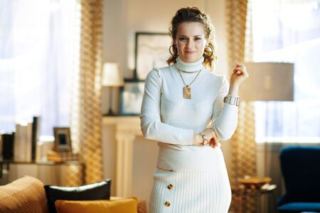 elegant 40 years old woman in white sweater and skirt standing at modern home in sunny winter day.