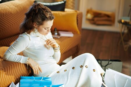 concerned young woman in white sweater and skirt sitting near divan with shopping bags at modern home in sunny winter day.