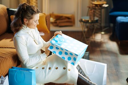 happy stylish housewife in white sweater and skirt in the modern living room in sunny winter day sitting near couch looking inside shopping bag.