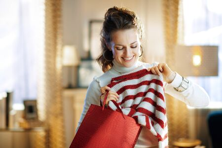 smiling middle age housewife in white sweater and skirt with red shopping bag checking purchased sweater at modern home in sunny winter day.