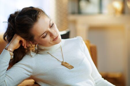 Portrait of unhappy modern 40 years old woman in white sweater and skirt in the modern house in sunny winter day and.
