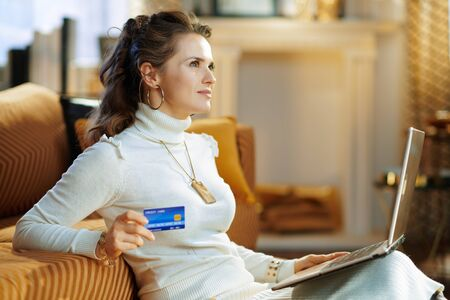 smiling stylish middle age woman in white sweater and skirt with credit card making online shopping on e-commerce website in the modern living room in sunny winter day.