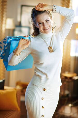 smiling trendy 40 years old woman in white sweater and skirt with blue shopping bags at modern home in sunny winter day.