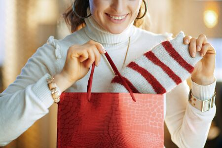 Closeup on smiling elegant female in white sweater and skirt with red shopping bag taking out purchased sweater at modern home in sunny winter day. Banque d'images