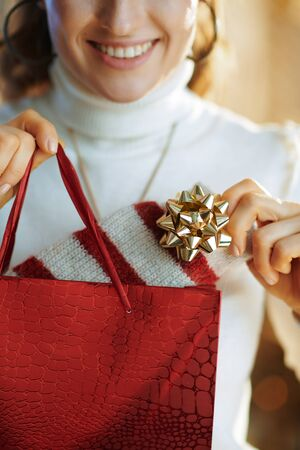 Closeup on happy trendy middle age woman in white sweater and skirt with red shopping bag taking out purchased sweater in the modern house in sunny winter day.