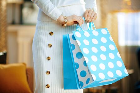 Closeup on trendy middle age housewife in white sweater and skirt in the modern living room in sunny winter day holding blue shopping bags.