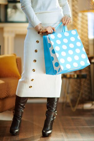 Closeup on elegant 40 years old woman in white sweater and skirt at modern home in sunny winter day holding blue shopping bags.