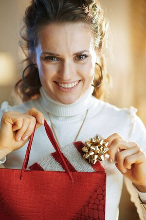 Portrait of happy young woman in white sweater and skirt with red shopping bag taking out purchased sweater in the modern house in sunny winter day. Stockfoto