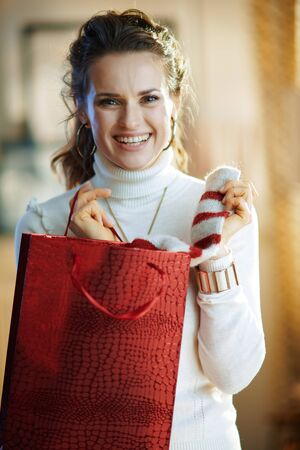 Portrait of happy stylish woman in white sweater and skirt with red shopping bag taking out purchased sweater at modern home in sunny winter day.