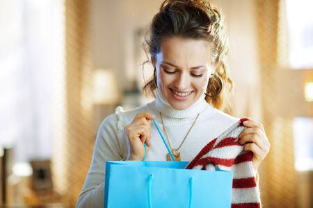 happy trendy housewife in white sweater and skirt with blue shopping bag checking purchased sweater in the modern house in sunny winter day.