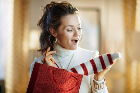 surprised modern middle age woman in white sweater and skirt with red shopping bag taking out purchased sweater in the modern living room in sunny winter day.