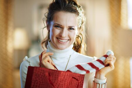 Portrait of smiling elegant woman in white sweater and skirt with red shopping bag taking out purchased sweater in the modern living room in sunny winter day.