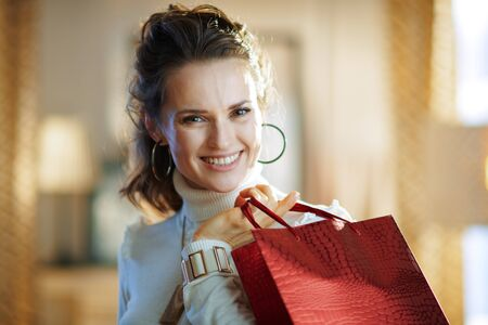 Portrait of smiling elegant 40 years old woman in white sweater and skirt with red shopping bag in the modern house in sunny winter day.