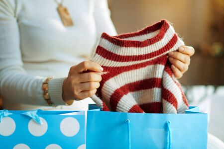 Closeup on trendy 40 years old housewife in white sweater and skirt with shopping bags checking bought sweater in the modern house in sunny winter day.