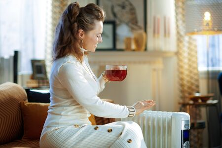 happy modern woman in white sweater and skirt at modern home in sunny winter day sitting on couch near white electric oil radiator and drinking cup of hot tea.