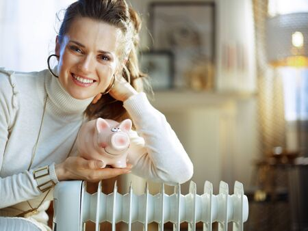 Portrait of happy elegant woman in white sweater and skirt in the modern living room in sunny winter day sitting on couch near white electric oil radiator holding piggy bank.