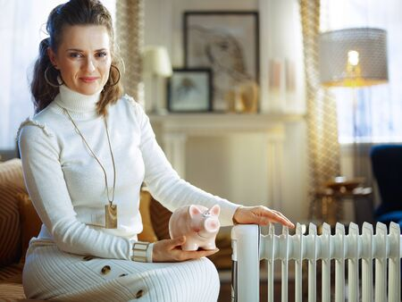 smiling modern woman in white sweater and skirt at modern home in sunny winter day sitting on couch near white electric oil radiator holding piggy bank. Stock Photo