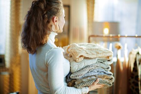 Seen from behind stylish middle age housewife in white sweater and skirt in the modern house in sunny winter day holding pile of sweaters.