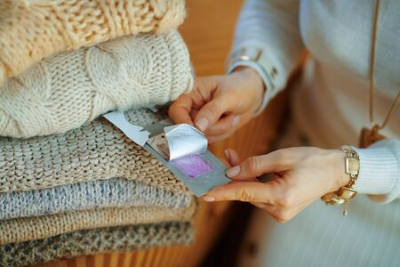 Closeup on young female in white sweater and skirt sitting near couch with pile of sweaters and using cloth anti moth lavender wardrobe repellent at modern home in sunny winter day.