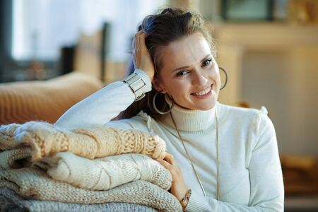 Portrait of smiling stylish woman in white sweater and skirt sitting near couch with pile of sweaters in the modern living room in sunny winter day. Stock Photo