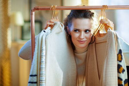 pensive trendy 40 years old housewife in white sweater and skirt at modern home in sunny winter day in good mood choosing sweaters hanging on copper clothes rack. Stock Photo
