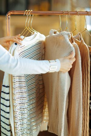 Closeup on elegant 40 years old woman in white sweater and skirt in the modern house in sunny winter day choosing sweaters hanging on copper clothes rack.