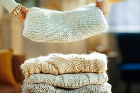 Closeup on modern female in white sweater and skirt at modern home in sunny winter day prepare sweaters pile for storage.