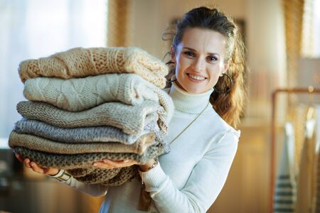 happy stylish female in white sweater and skirt in the modern living room in sunny winter day showing pile of sweaters.