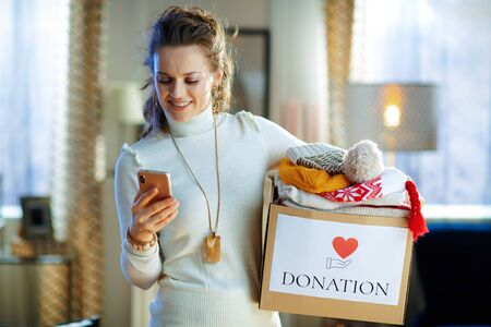 happy young female in white sweater and skirt with donation box with old warm clothes using app on smartphone in the modern living room in sunny winter day.