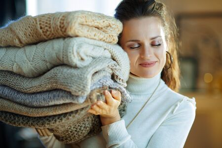 smiling modern 40 years old housewife in white sweater and skirt in the modern living room in sunny winter day holding pile of sweaters. Stock Photo