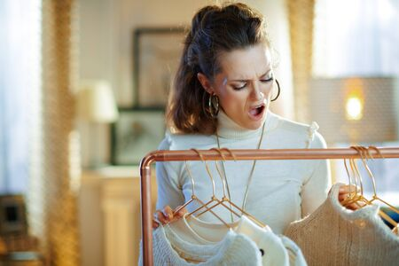 shocked modern housewife in white sweater and skirt at modern home in sunny winter day choosing sweaters hanging on copper clothes rack and doesnt find something suitable. Stock Photo