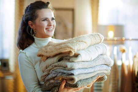 happy stylish woman in white sweater and skirt in the modern living room in sunny winter day holding pile of sweaters. Stock Photo