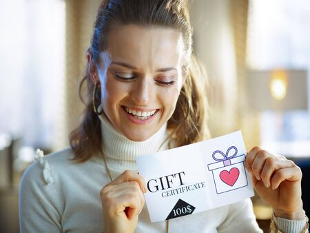 smiling middle age woman in white sweater and skirt with gift certificate at modern home in sunny winter day.