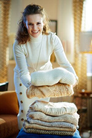 smiling elegant woman in white sweater and skirt in the modern house in sunny winter day prepare sweaters pile for storage.